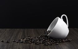 Coffee beans in white cup. On wooden table, black background Stock Image