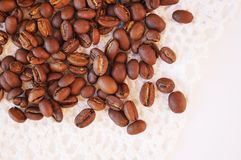 Coffee beans on a white knitted napkin royalty free stock photography