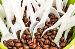 Coffee Beans with white plastic Spoons. Close up of coffee beans with a white plastic spoon in a green box Royalty Free Stock Photography