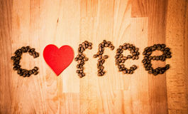 Coffee beans on wood background. Shape of word Coffee made from coffee beans, decorated with red heart on wooden surface. Royalty Free Stock Photo