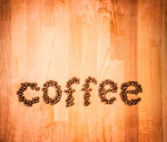 Coffee beans on wood background. Shape of word Coffee made from coffee beans, decorated with red heart on wooden surface. Royalty Free Stock Image