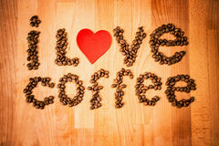 Coffee beans on wood background. Shape of word Coffee made from coffee beans, decorated with red heart on wooden surface. Royalty Free Stock Photography