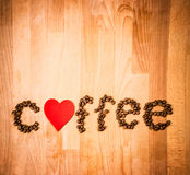 Coffee beans on wood background. Shape of word Coffee made from coffee beans, decorated with red heart on wooden surface. Stock Photos
