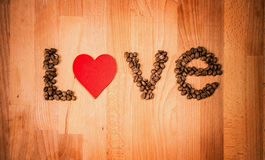 Coffee beans on wood background. Shape of word Love made from coffee beans, decorated with red heart on wooden surface. Royalty Free Stock Photos