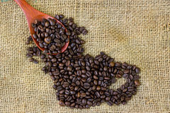 Coffee beans on wood spoon and Burlap Royalty Free Stock Image