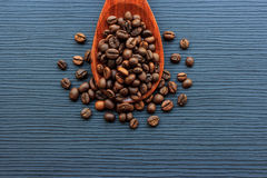 Coffee beans and wood spoon on dark wood Stock Images