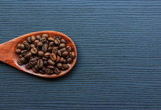 Coffee beans and wood spoon on dark wood Royalty Free Stock Photos