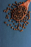 Coffee beans and wood spoon on dark wood Stock Photos