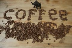 Coffee beans on a wooden background and the word `coffee` from coffee beans stock images