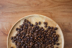 Coffee beans and wooden bowl on the brown table Stock Photos