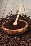 Coffee beans and wooden bowl full of ground coffee Stock Photography