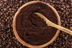 Coffee beans and wooden bowl full of ground coffee Stock Photo