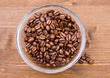 Coffee beans on wooden bowl on top. Coffee beans on bowl on wooden table seen from above Stock Images