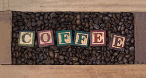 Coffee beans in an wooden box coffee grains with wooden on text is coffee.  Stock Photos