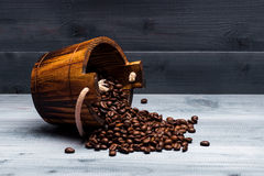 Coffee beans on wooden cask. Coffee beans set up on wooden cask on vintage wooden background. Side view Stock Images