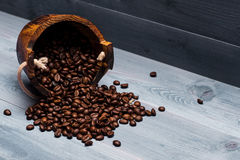 Coffee beans on wooden cask. Coffee beans set up on wooden cask on vintage wooden background. Side view Stock Photo