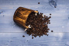 Coffee beans on wooden cask. Coffee beans set up on wooden cask on vintage wooden background. Top view Royalty Free Stock Photo