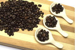 Coffee beans on wooden chopboard.  Royalty Free Stock Images