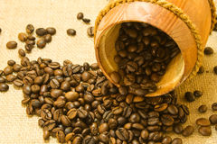 Coffee beans in a wooden keg. Coffee beans spilled from a lying wooden jar on the background of a sacking Stock Image
