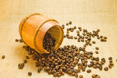 Coffee beans in a wooden keg. Coffee beans spilled from a lying wooden jar on the background of a sacking Stock Photography