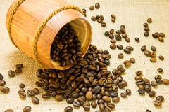 Coffee beans in a wooden keg. Coffee beans spilled from a lying wooden jar on the background of a sacking Royalty Free Stock Image