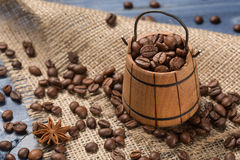 Coffee-beans in a wooden pail on burlap. Coffee cereal piled on sackcloth, spices, cinnamon and tubby, boards of blue color royalty free stock photography
