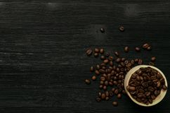 Coffee beans in wooden pot on black wooden table. Coffee beans in wooden pot jar and scattered coffee beans isolated on black wooden table surface background Stock Image