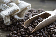 Coffee beans with wooden scoop and linen bag on wooden table. Coffee beans with wooden spoon and linen bag on wooden table Stock Image
