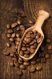 Coffee beans in a wooden scoop on wood Royalty Free Stock Image