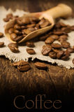 Coffee beans in a wooden scoop on wooden background Royalty Free Stock Photo