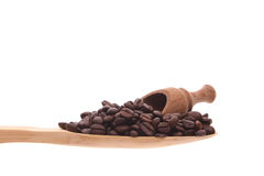 Coffee beans on a wooden spoon. Coffee beans simply offered on a wooden spoon isolated on a white background Stock Photo