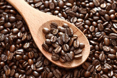 Coffee beans in a wooden spoon. On a coffee beans background. Close-up Stock Photography