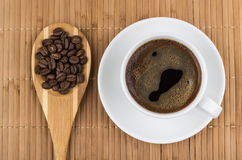 Coffee beans in wooden spoon and cup of espresso Stock Photography
