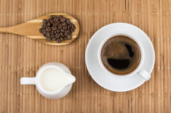 Coffee beans in wooden spoon, jug milk and  espresso Stock Photo