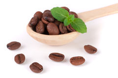 Coffee beans in a wooden spoon with leaf isolated on a white background.  Stock Photo
