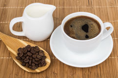 Coffee beans in wooden spoon, milk and cup of espresso Royalty Free Stock Photos