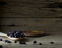 Coffee beans in wooden spoon on old wood background. Royalty Free Stock Photo