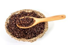 Coffee beans on wooden spoon over basket. Of coffee beans on white background Stock Photos