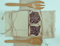 Coffee beans and wooden spoon on sack surface. Royalty Free Stock Images