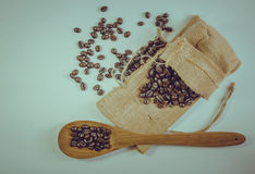 Coffee beans and wooden spoon on sack surface. Stock Photos