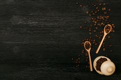 Coffee beans in wooden spoons and coffee in a wooden pot. Coffee beans in wooden spoons and coffee in a wooden pot isolated on black wooden table surface Royalty Free Stock Photography
