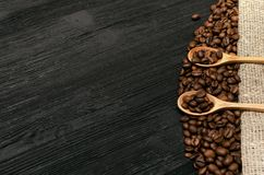 Coffee beans in wooden spoons. Coffee beans in wooden spoons on sackcloth burlap canvas and coffee scattered on a black table surface background with copy space Royalty Free Stock Photography