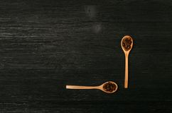 Coffee beans in wooden spoons scoops. Coffee beans in wooden spoons and coffee scattered on a black table surface background with copy space. Top view Royalty Free Stock Photo