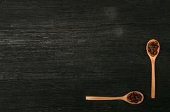 Coffee beans in wooden spoons scoops. Coffee beans in wooden spoons and coffee scattered on a black table surface background with copy space. Top view Royalty Free Stock Image