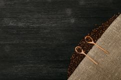 Coffee beans in wooden spoons scoops on the table. Coffee beans in wooden spoons on sackcloth burlap canvas and coffee scattered on a black table surface Stock Image