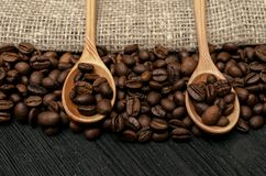 Coffee beans in wooden spoons scoops on the table. Coffee beans in wooden spoons on sackcloth burlap canvas and coffee scattered on a black table surface Royalty Free Stock Images