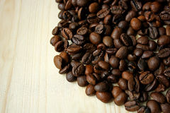 Coffee beans on wooden surface. Royalty Free Stock Image