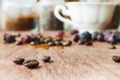 Coffee beans on the wooden table. Coffee beans on the background of wood texture Royalty Free Stock Images