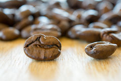 Coffee beans on wooden table closeup. Royalty Free Stock Image