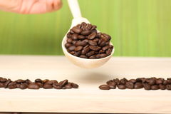Coffee beans on wooden table with spoon Stock Images